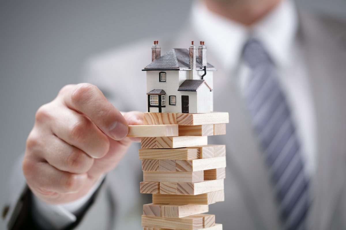 model house on a Jenga stack illustrating the like-kind exchange rules risk in 2017