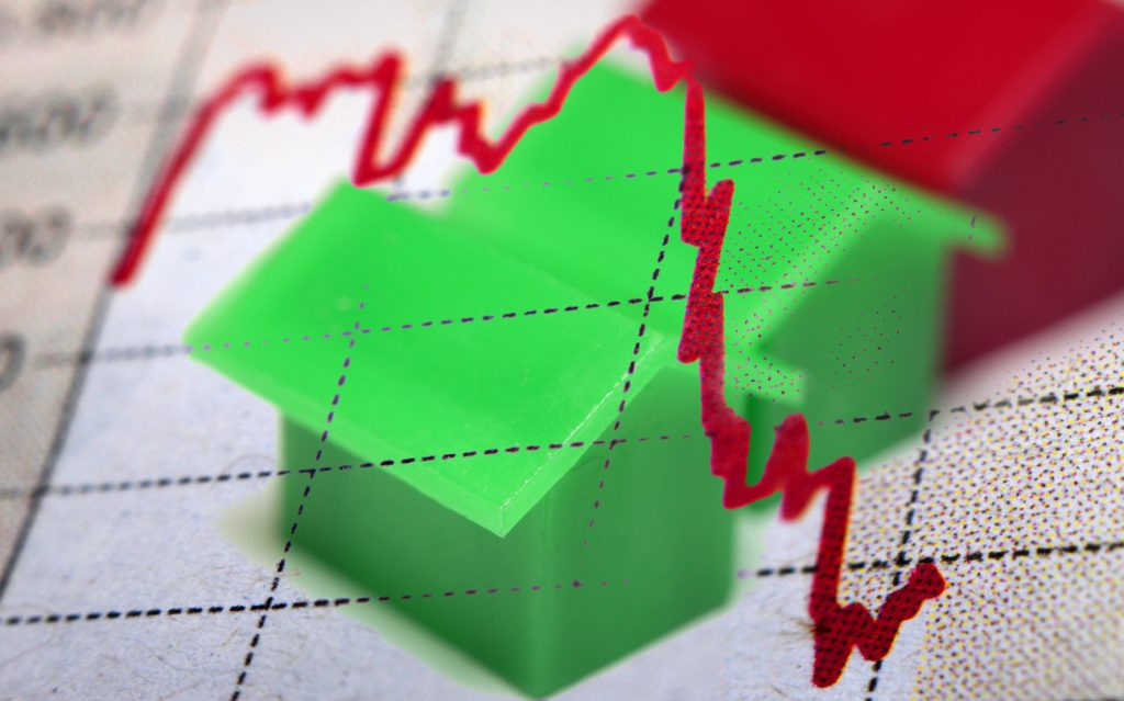 Real estate market graph trending downwards over model houses